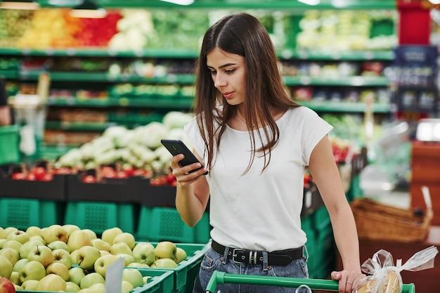 Groenten en fruit. vrouwelijke shopper in vrijetijdskleding in markt op zoek naar producten.