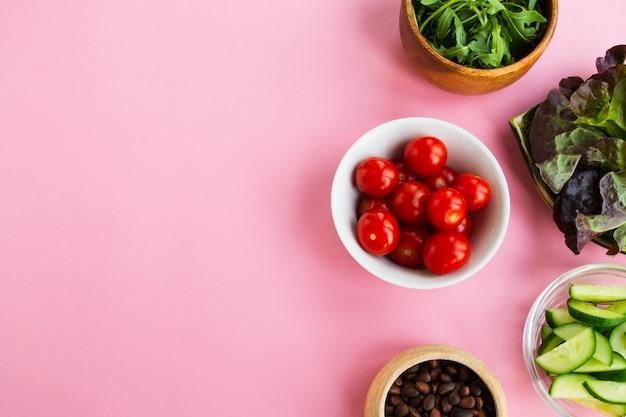 Groenten en noten op een roze achtergrond. ruimte voor tekst