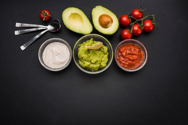 Groenten en sauzen in kommen dichtbij lepels