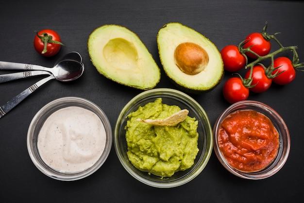 Groenten en set van sauzen in kommen in de buurt van lepels