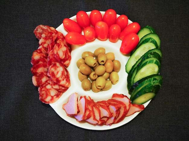 Groenten en vlees op een plaat. een snelle snack voor gasten. witte plaat tegen een donkere muur