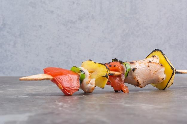 Groenten en vlees op spiesjes, op het marmer.