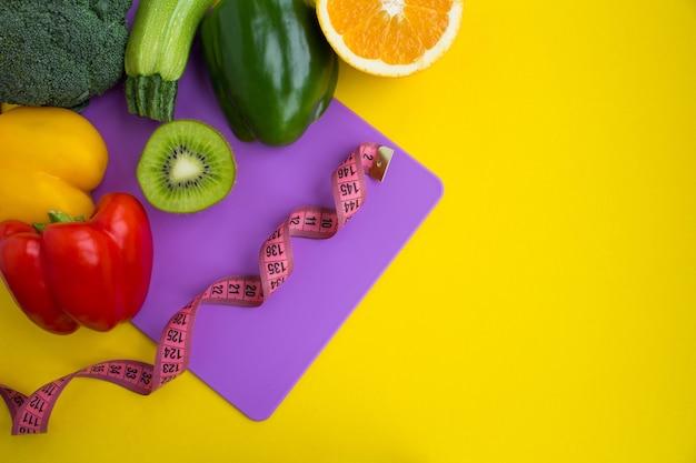 Groenten, fruit en roze centimeter op de violette snijplank op geel