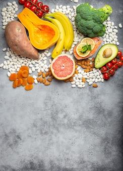 Groenten, fruit en voedingsmiddelen die kalium bevatten, stenen achtergrond, bovenaanzicht, ruimte voor tekst. natuurlijke bronnen van kalium, vitamines en micronutriënten, gezonde evenwichtige voeding, preventie van avitaminose
