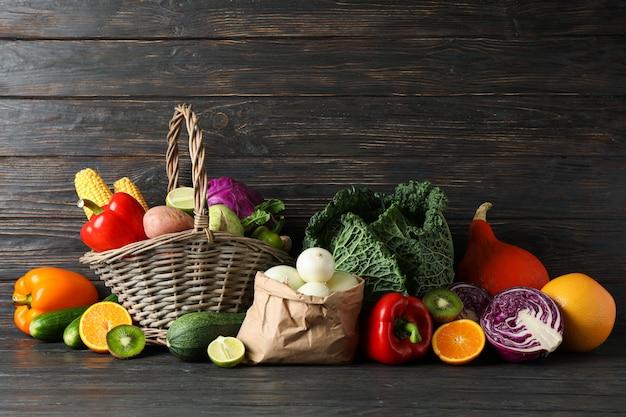 Groenten, fruit, rieten mand en papieren zak op hout