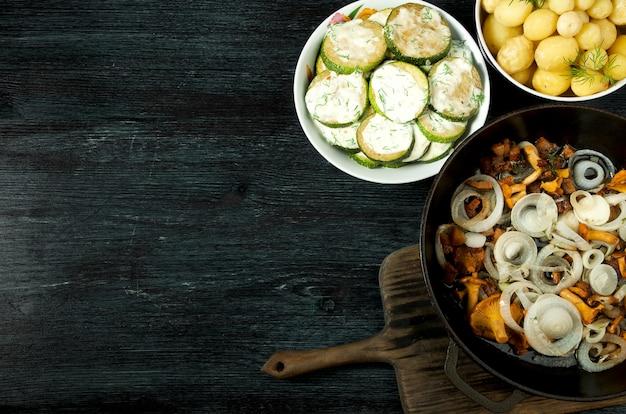 Groenten. gebakken courgettesaus in een plaat. jonge gekookte aardappelen met dille in een kom. gebraden cantharelpaddestoelen met gouden uien in een pan. copyspace