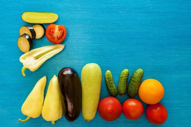 Groenten geheel en gesneden op een blauw bord.