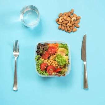 Groenten healhy salade voor kantoorlunch in container op blauwe lijst.