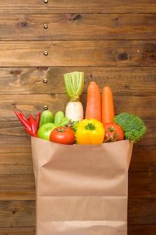 Groenten in de boodschappentas op houten muur