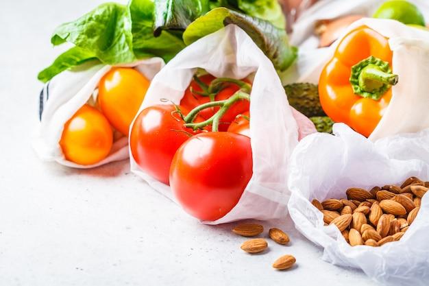 Groenten in ecologische katoenen zakken, paprika, tomaat, sla, komkommer, limoen, ui en noten.