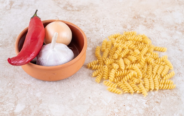 Groenten in een kleine kom naast een stapel rauwe pasta
