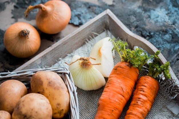 Groenten in een mand: bieten, uien, knoflook, dille, aardappelen, wortelen op een oude houten achtergrond