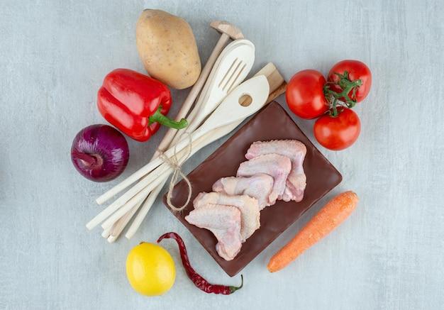 Groenten, keukengereedschap en rauwe kippenvleugels op grijze ondergrond.