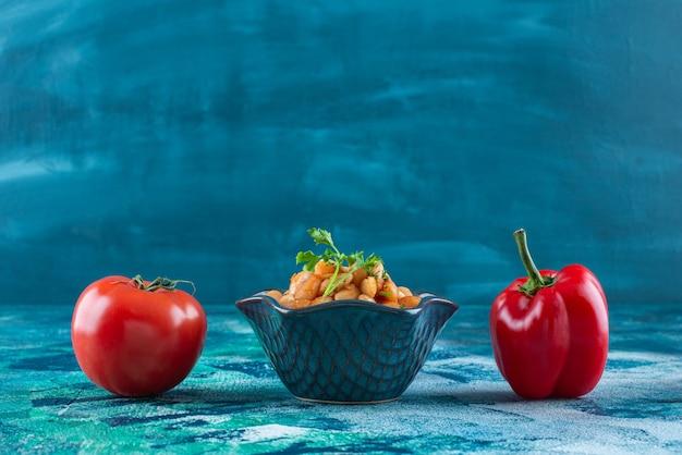 Groenten met een kom gebakken bonen, op de blauwe achtergrond.
