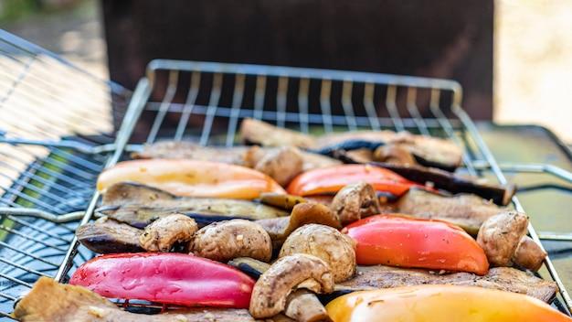 Groenten op de grill close-up. aubergines, paprika's, champignons en knoflook worden geroosterd boven houtskool. vegetarische grill.