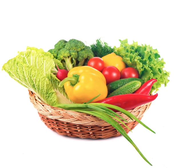 Groenten op de witte achtergrond - broccoli, tomaten, komkommers en groene uien. samenstelling van groenten op de witte achtergrond