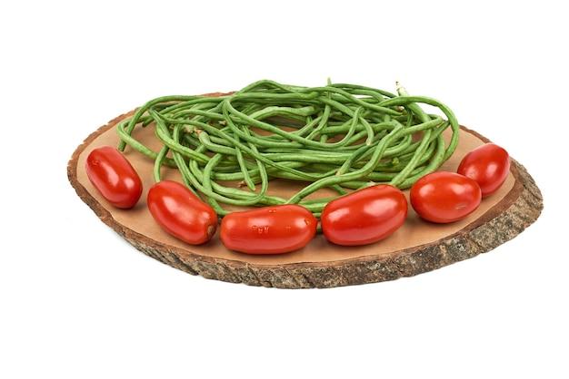 Groenten op een houten bord op het wit.