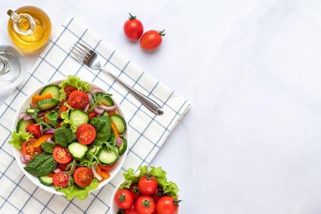 Groenten op een witte plaat op een grijze marmeren achtergrond. bovenaanzicht. salade gemaakt met kerstomaatjes, komkommers, rucola, basilicum en aangekleed met olijfolie. gezond voedselconcept, een veganistisch dieet. ruimte kopiëren