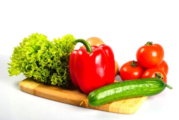 Groenten op hardboard in keuken voor salade, die op wit wordt geïsoleerd