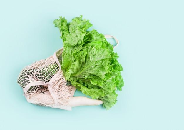 Groenten, spinazie bladeren, sla, groene uien, radijs, kool in een string boodschappentas voor voedsel. zero waste