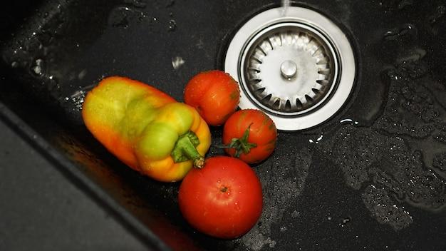 Groenten - tomaten en paprika's in een zwarte gootsteen onder water. het concept van vers en gezond voedsel