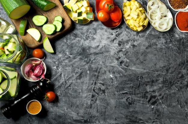 Groenten. verse groenten (komkommers, tomaten, uien, knoflook, dille, sperziebonen) op een grijze achtergrond. bovenaanzicht copyspace
