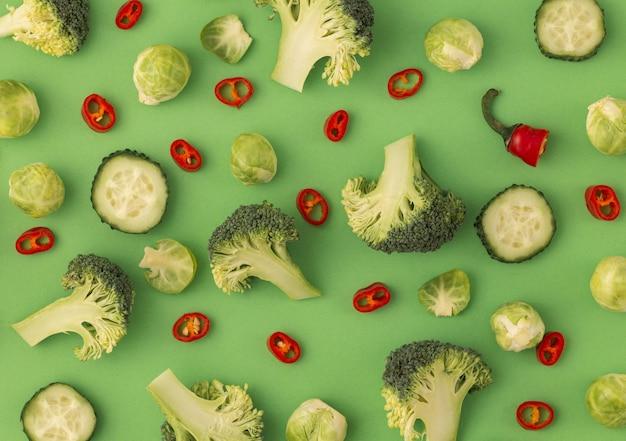 Groenten voedselpatroon gemaakt van broccoli, spruitjes, komkommer, chili peper, groene achtergrond. creatief minimaal plat ontwerp over voeding, gezond eten, diëten, vitamines. bovenaanzicht