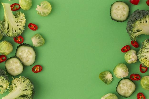 Groenten voedselpatroon gemaakt van broccoli, spruitjes, komkommer, chili peper, groene achtergrond. minimaal plat ontwerp van voeding, gezond eten, diëten, vitamines. bovenaanzicht, ruimte voor tekst