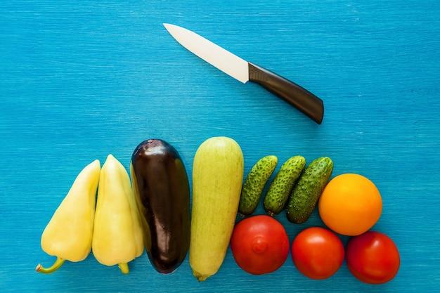Groenten zijn heel en snijd een notitieblok voor het schrijven van rijst en een keramisch mes op een blauw bord.