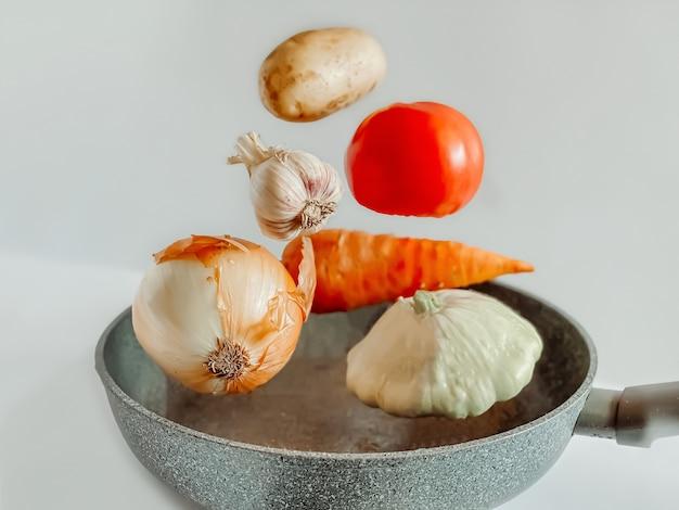 Groenten zwevend boven een koekenpan voor een groentestoofpot. koken concept.