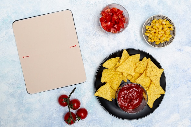 Groentennotitieboekje en nachos met ketchup in zwarte kom