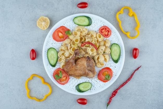 Groentensalade op witte plaat met heerlijke macaroni op marmeren achtergrond