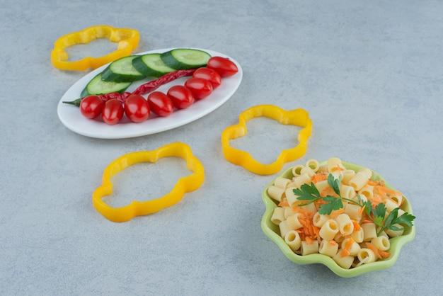 Groentensalade op witte plaat met macaroni op marmeren achtergrond. hoge kwaliteit foto