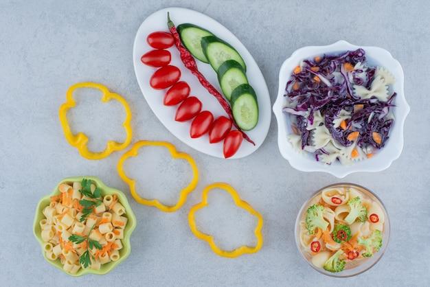 Groentensalade op witte plaat met macaroni op marmeren oppervlakte