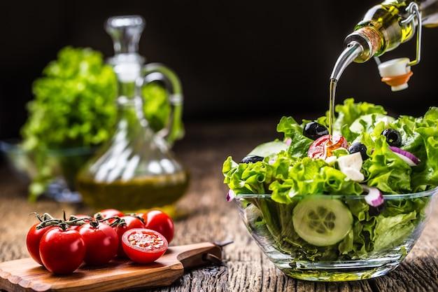 Groentenslasalade met tomatenuienkaas en olijven olijfolie die in kom salade gieten