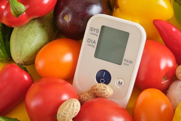 Groententonometer op een gele achtergrondexemplaarruimte, digitale bloeddrukmeter. goed en gezond voedingsconcept