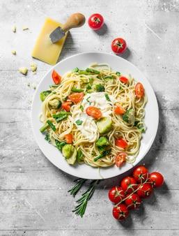 Groentepasta met broccoli, tomaten, sperziebonen en parmezaanse kaas. op witte houten tafel