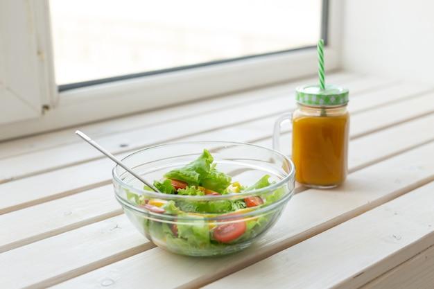 Groentesalade en fruitsmoothies liggen op een witte vensterbank. concept van een gezonde fysieke levensstijl