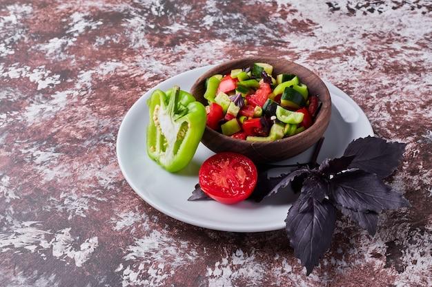 Groentesalade in een houten kop op het marmer in het midden, hoekmening.