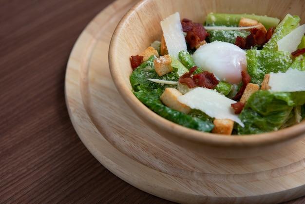 Groentesalade in een lichtbruine kom met eieren, brood en spek op de schotel op bruine grond