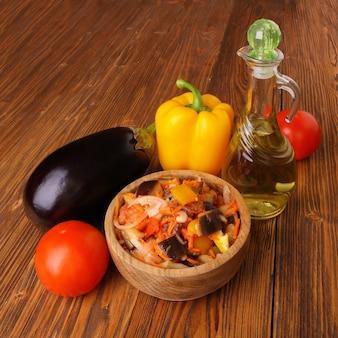 Groentesalade met aubergine en andere ingrediënten op een houten tafel