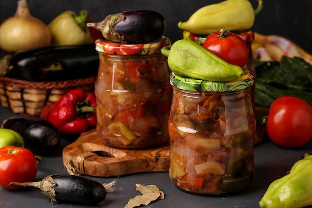 Groentesalade met aubergine, uien, paprika en tomaten in potten