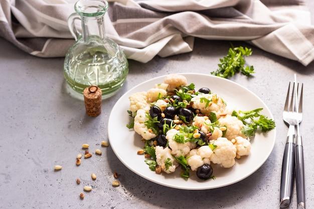Groentesalade met bloemkool, olijven, peterselie en pijnboompitten