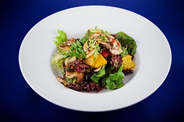 Groentesalade met champignons, paprika, uien, sla en saus met mosterdzaadjes. plat lag bovenaanzicht op een witte plaat op een blauwe achtergrond.