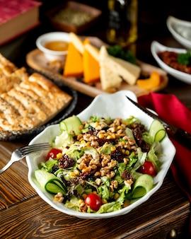Groentesalade met gedroogde pruimen, noten en maïs