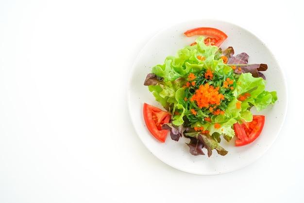 Groentesalade met japans zeewier en garnaleneieren op witte lijst