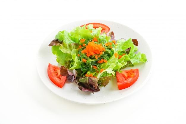Groentesalade met japanse zeewier en garnalen eieren op wit oppervlak