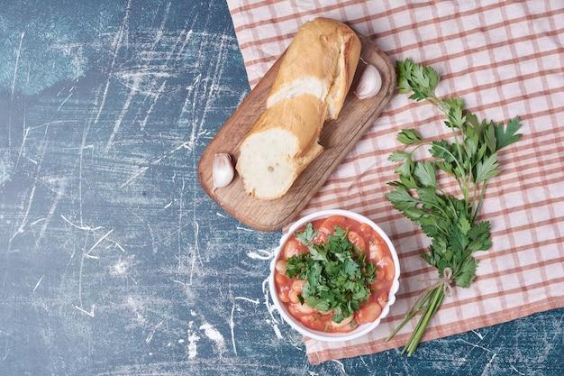 Groentesalade met kruiden en specerijen geserveerd met stokbrood.