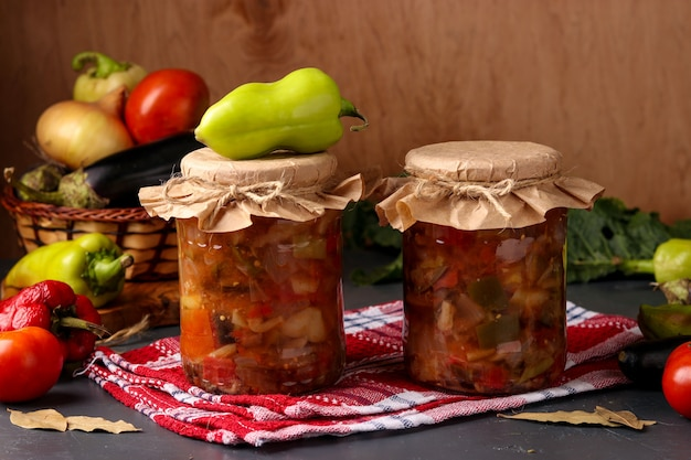 Groentesalade met paprika, aubergine, uien en tomaten in potten op een houten tafel, horizontale oriëntatie