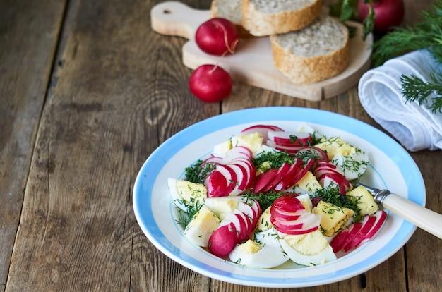 Groentesalade met radijs, dille en eieren op een houten tafel